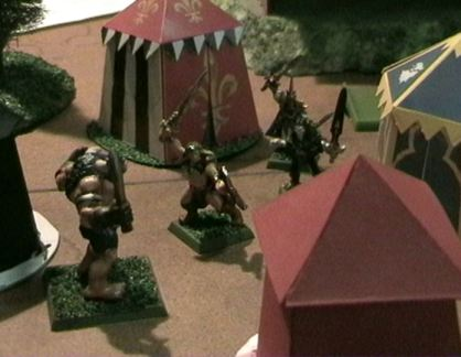 Aragorn attacks a Minotaur in a camp.